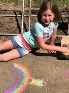 girl drawing outside with chalk her idea of the universe.